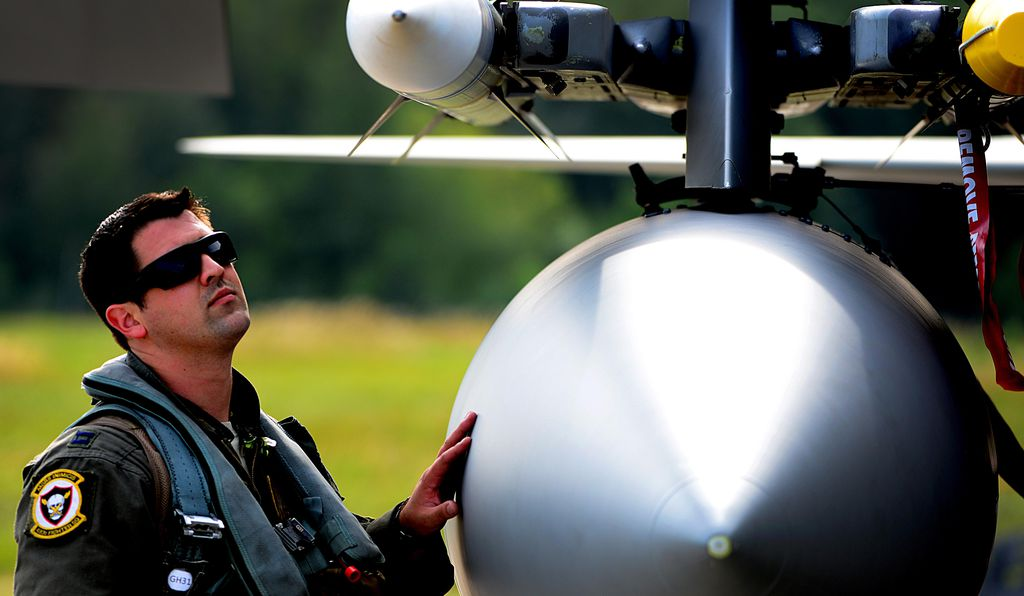 Such interceptions are peaceful, but the missiles are real. During a 2017 Baltics deployment, an F-15 pilot (left) inspects the fighter's AIM‑120.